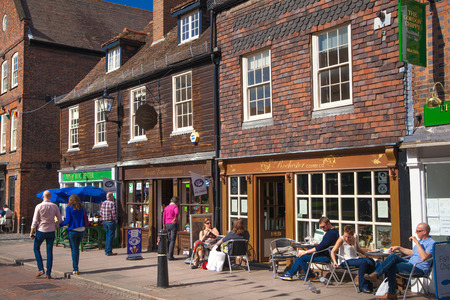 typically english: ROCHESTER, UK - MAY 16, 2015: Rochester high street at weekend. People walking through the street, passing cafes, restaurants and shops Editorial