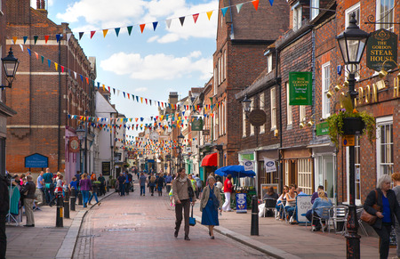typically british: ROCHESTER, UK - MAY 16, 2015: Rochester high street at weekend. People walking through the street, passing cafes, restaurants and shops Editorial