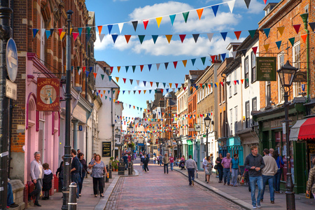 'english: ROCHESTER, UK - MAY 16, 2015: Rochester high street at weekend. People walking through the street, passing cafes, restaurants and shops Editorial