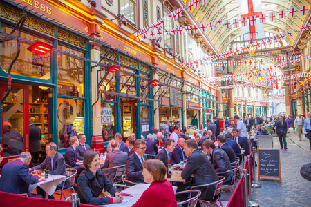 british people: LONDON, UK - APRIL 22, 2015: Leadenhall market decorated with British flags and lots of business people having a lunch.