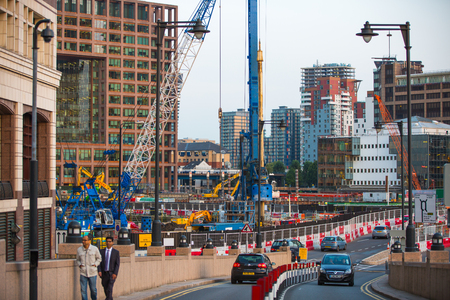 condo construction: LONDON, UK - SEPTEMBER 9, 2015: Building construction site with cranes and industrial units  in Canary Wharf aria