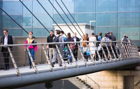 lots people: LONDON, UK - SEPTEMBER 9, 2015: Lots of people crossing bridge on the way to work. Canary Wharf business life