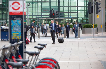 business life: LONDON, UK - SEPTEMBER 9, 2015: Office workers going home after working day in Canary Wharf. Business life of London