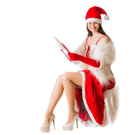 femme brune sexy: Belle jeune femme à l'article costume de Père Noël lire la lettre de Noël. Noël fond Banque d'images