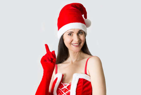 red hat: Beautiful young woman portrait in Santa Clause costume. Christmas background