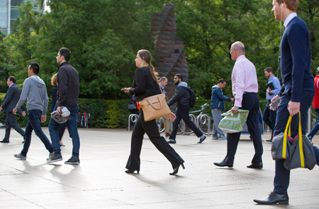 going: LONDON, UK - SEPTEMBER 14, 2015:  Office workers going to work. Early morning hours in Canary Wharf business life Editorial