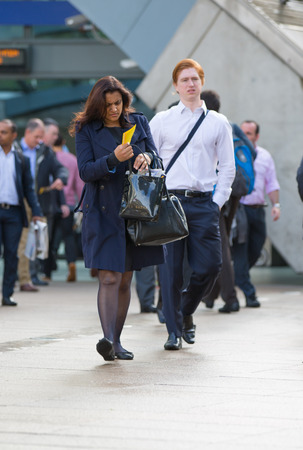 going: LONDON, UK - SEPTEMBER 14, 2015:  Young women going at work. Early morning hours in Canary Wharf business life