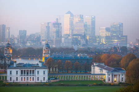 London, UK - October 31, 2015:  Panorama of Canary Wharf in night. View includes the park, Royal chapel, Painted hall and green light of Greenwich zero tome meridian