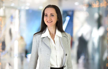 white suit: Beautiful business woman portrait in office against of glass reflection Stock Photo