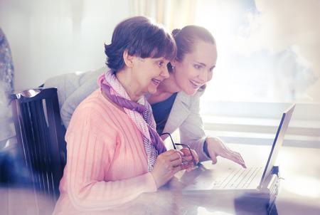 amicizia: Giovane donna aiutare un anziano con un computer portatile per la ricerca su Internet. Generazioni giovani e di età di pensione che lavorano insieme.