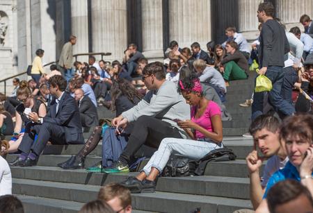 gente sentada: LONDRES, Reino Unido - 10 de septiembre, 2015: Un montón de gente sentada en las escaleras de st. Paul catedral