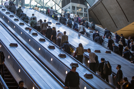 business life: LONDON, UK - SEPTEMBER 14, 2015: Lots of people going up to escalator in Canary Wharf, modern business life concept