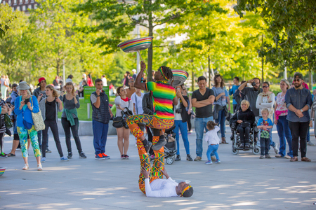people watching: LONDON, UK - SEPTEMBER 10, 2015:  Street performance by Africans artists at south embankment of the River Thames. Lots of people watching the show at the background