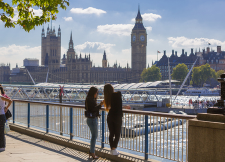 embankment: LONDON, UK - SEPTEMBER 10, 2015: Young girl watching Big Ben and Houses of Parliament. View from the River Thames embankment