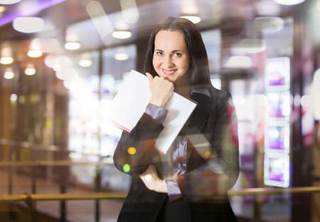 successful woman: Successful business woman smiling portrait with note pad. Portrait in office against of glass reflection