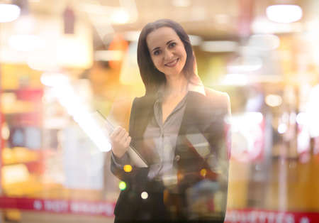 Successful business woman smiling portrait with note pad. Portrait in office against of glass reflection