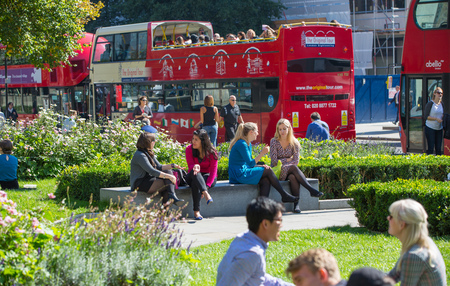 out to lunch: LONDON, UK - SEPTEMBER 10, 2015: Red british buses and park in the City of London. Lunch time, people getting out of offices Editorial