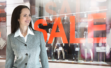 on special offer: Young beautiful woman posing against Sale window display background. Stock Photo
