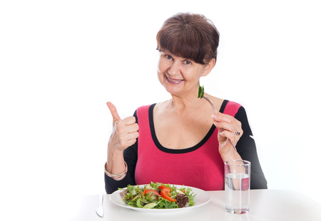 acqua bicchiere: Elderly good looking woman eating green salad. Healthy life style concept
