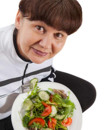 стиль жизни: Пожилая женщина в спортивном костюме едят зеленый салат. Концепция здорового образа жизни