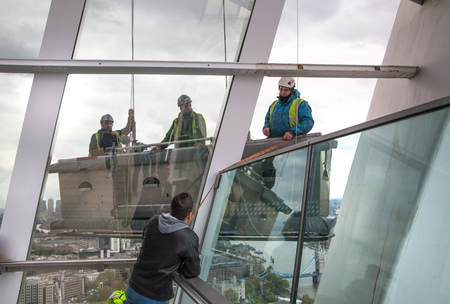 steeplejack: LONDON, UK - APRIL 22, 2015: Building maintenance brigade in lift operating platform over the City of London Editorial