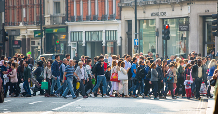 LONDON, UK - OCTOBER 4, 2016: Crowd of people crossing the road on the Regent street. Tourists, shoppers and business people rush time Editorial