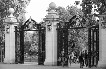 main gate: LONDON, UK - OCTOBER 4, 2016: Main entrance to the Green park with people passing the gate
