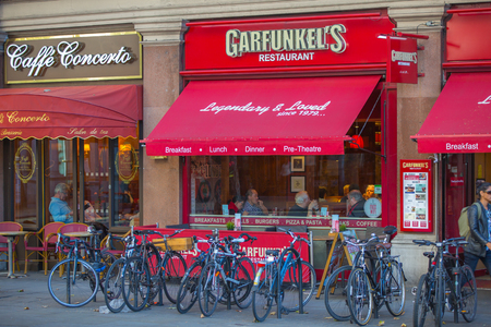 parked bikes: ONDON, UK - SEPTEMBER 10, 2015: Cafe at the Trafalgar street with parked bikes on the side