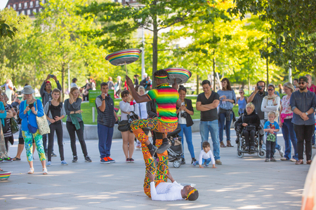 show cases: LONDON, UK - SEPTEMBER 10, 2015: Street performance by Africans artists at south embankment of the River Thames. Lots of people watching the show at the background