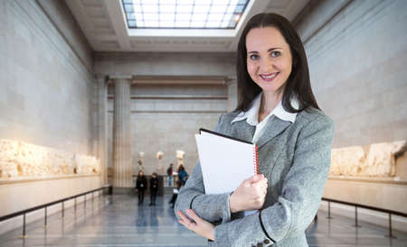 international business: Attractive young woman with notepad in exhibition hall