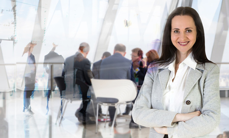 negocios internacionales: Mujer joven atractiva en oficina contra de la reflexión de vidrio y reunión de negocios va en el fondo Foto de archivo