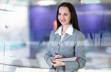woman business suit: Attractive woman in suit with note pad in the office against of glass reflection. Business background. Stock Photo