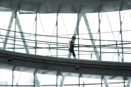 go inside: Walking people blur. Modern architectural interior Editorial