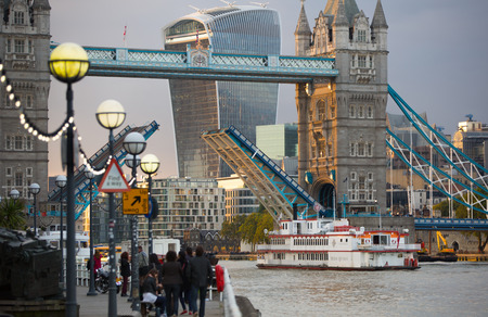 night dusk: LONDON, UK - SEPTEMBER 19, 2015: Tower bridge open for boats  and City of London at dusk and first night lights.  View includes Gherkin and other buildings at the background Editorial