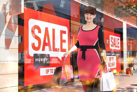 tienda de ropa: bolsas atractivas mayores mujer que sostiene comerciales, contra la ventana de la pantalla Venta Foto de archivo