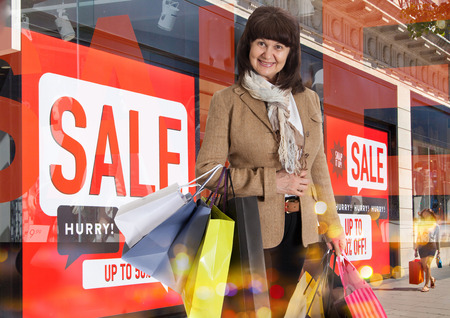 christmas promotion: Attractive elderly woman holding shopping bags, against of Sale window displayv