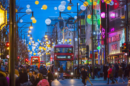 business christmas: LONDON, UK - DECEMBER 30, 2015: Christmas lights decoration at Oxford street and lots of people walking during the Christmas sale, public transport, buses and taxies