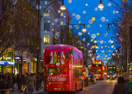london people: LONDON, UK - DECEMBER 30, 2015: Christmas lights decoration at Oxford street and lots of people walking during the Christmas sale, public transport, buses and taxies