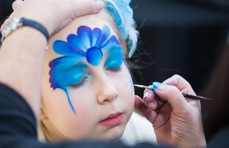 baby face: Christmas face painting, Portrait of little girl during the face painting session Stock Photo