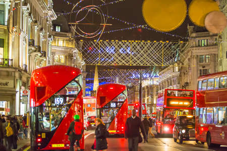 bargain hunting: LONDON, UK - DECEMBER 30, 2015: Christmas lights decoration at Regent street and lots of people walking during the Christmas sale and public transport, buses and taxies