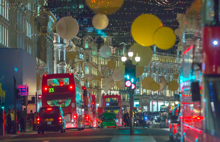 taxi famous building: LONDON, UK - DECEMBER 30, 2015: Christmas lights decoration at Regent street and lots of people walking during the Christmas sale and public transport, buses and taxies