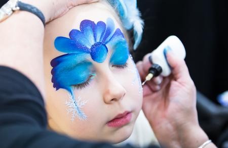 Kerst gezicht schilderen, Portret van een meisje tijdens het gezicht schilderij sessie Stockfoto