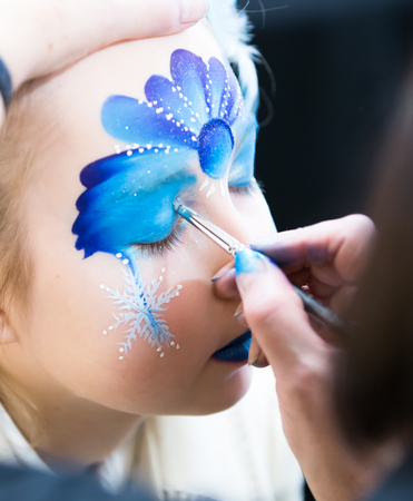 glamour girl: Christmas face painting, Portrait of little girl during the face painting session Stock Photo