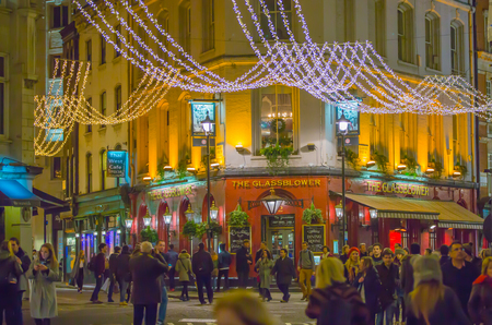 regent: LONDON, UK - DECEMBER 30, 2015: Christmas lights decoration at Regent street and lots of people walking during the Christmas sale