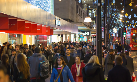 LONDON, UK - DECEMBER 30, 2015: Oxford street view with Christmas lights decorating, lots of people shopping around and public transport, busses and taxies. Christmas rush, modern life concept