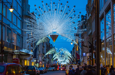 bargain hunting: LONDON, UK - DECEMBER 30, 2015: Christmas lights decoration at Oxford street and lots of people walking during the Christmas sale, public transport, buses and taxies