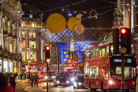 bargain hunting: LONDON, UK - DECEMBER 30, 2015: Oxford street view with Christmas lights decorating, lots of people shopping around and public transport, busses and taxies. Christmas rush, modern life concept