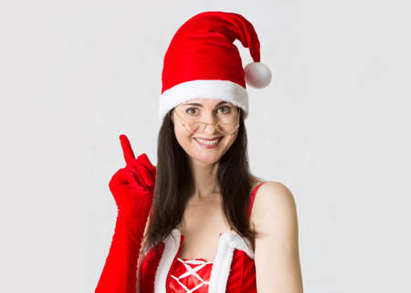 female christmas: Attractive woman in Santa costume blowing at snowflakes. Background template