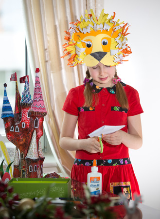 art and craft: Little girl demonstrating her art craft works, Paper masher fairy castle and Lion mask she made. Educational and creative concept. Stock Photo
