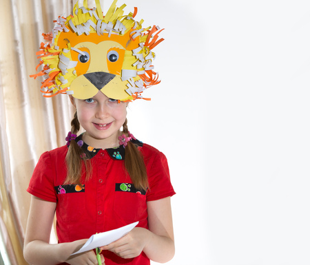 art and craft: Little girl demonstrating her art craft works, Paper Lion mask she made. Educational and creative concept.